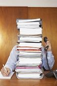 Obscured office worker using telephone while writing document behind a stack of folders at desk