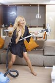 Happy blonde woman using vacuum cleaner as guitar, having fun at home in living room, laughing.