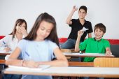 Playful schoolboys throwing paperplane and paperball on girl in classroom