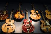 picture of musical instrument string  - A wall with vintage guitars hanging on display - JPG