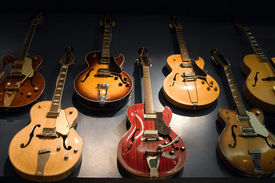 pic of musical instrument string  - A wall with vintage guitars hanging on display - JPG
