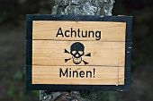 stock photo of landmines  - German land mines warning sign from World War Two wet with water droplets - JPG
