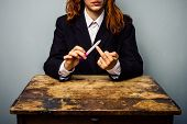 stock photo of obscene  - Businesswoman Displaying Obscene Gesture While Filing Her Nails - JPG