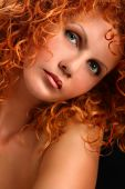 Portrait of beautiful redhead woman with rich curly hair looking at camera