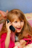 stock photo of goodnight  - young girl talking by phone on the bed - JPG