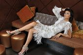 Model wearing couture dress lying on the sofa