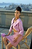 Model wearing couture pink suit posing on the rooftop