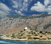 Old windmill on the shore of one of the Greek islands of the Dodecanese in the Aegean Sea, Greece