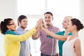 business, office, gesture and startup concept - smiling creative team doing high five gesture in off