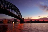 stock photo of crescent  - View across Sydney Harbour with Sydney Harbour Bridge arching across to North Sydney and a crescent moon and rich red dawn sunrise skies forming behind silhouetted buildings on the foreshore - JPG