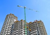 foto of building exterior  - Building crane and building under construction against blue sky - JPG