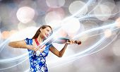 Young attractive woman in blue dress playing violin