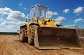 stock photo of wheel loader  - Front view of diesel wheel loader bulldozer with bucket pulled down outdoors - JPG