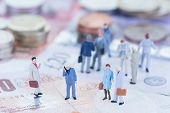 stock photo of british pound sterling note  - Miniature business people on Sterling banknotes close up