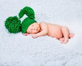 sweet newborn boy sleep in a green knitted hat