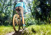 foto of riding-crop  - Young woman on mountain bike fast ride outdoors.