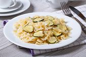Farfalle Pasta With Zucchini And Cheese On A White Plate