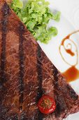 new york meat style beef steak fillet on white plate with hot chili pepper and green salad isolated