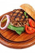 extra thick hot beef meat hamburger dinner on wooden plate with tomatoes and salad isolated on white