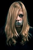 picture of kidnapped  - Portrait of scared kidnapped woman hostage with tape over her mouth - JPG