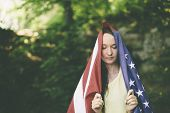 dreaming woman with the american flag  in the forest