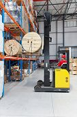 picture of forklift driver  - Forklift loading pallet with roll in distribution warehouse - JPG