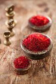 saffron spice in antique vintage iron bowls weights on wooden table