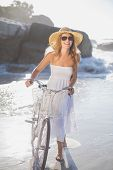 Beautiful smiling blonde in sundress with her bike at the beach on a sunny day