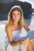 Beautiful smiling blonde in sundress using tablet on the beach on a sunny day