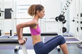 Fit woman exercising using the bench at the gym