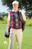 Golfer carrying his golf bag smiling at camera on a sunny day at the golf course