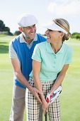 Golfing couple putting ball together smiling at camera each other on a sunny day at the golf course