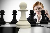 Composite image of focused businesswoman with magnifying glasses with chessboard