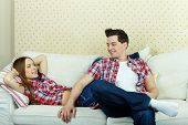 Happy couple in casual clothes having rest on sofa