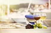 Pair of wineglasses and grapes against yachts in La Spezia, Italy