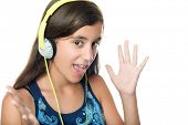 Hispanic teenage girl listening to music with an excited expression isolated on white
