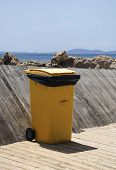 Yellow Trash Bin On Wood Jetty