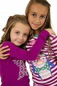 Two Girl Cousins Wearing Christmas Pajamas Hugging Each Other