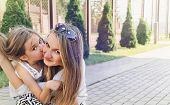 Little Cute Girl Kissing Her Beautiful Mum Outdoor In The Park