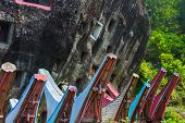 stock photo of burial  - Traditional burial site in Tana Toraja South Sulawesi Indonesia where coffins are placed in caves carved into the rock or in tongkonan decorated wooden buildings with outstanding boat shaped roof - JPG
