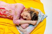 picture of pajamas  - girl in pajamas sleeping on the yellow sheet - JPG