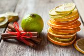 Stack Of Dried Orange And Lemon Slices, Lime And Cinnamon Sticks On Old Table.