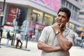 Portrait of a young asian indian businessman in city street