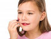 Little girl is applying lipstick on her cheek, isolated over white