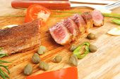red meat steak sliced on wooden board with cutlery isolated  over white background