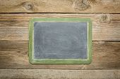 picture of slating  - blank slate blackboard against rustic weathered wood planks - JPG
