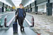 image of carry-on luggage  - Young businessman in formal suit carrying briefcase and luggage while standing in the airport hall - JPG