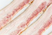 stock photo of bacon strips  - Three strips of fresh bacon close up