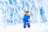 Child With Snow Shovel In Winter