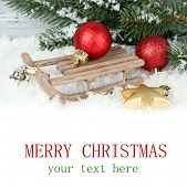 Wooden toy sledge with Christmas decor on light background